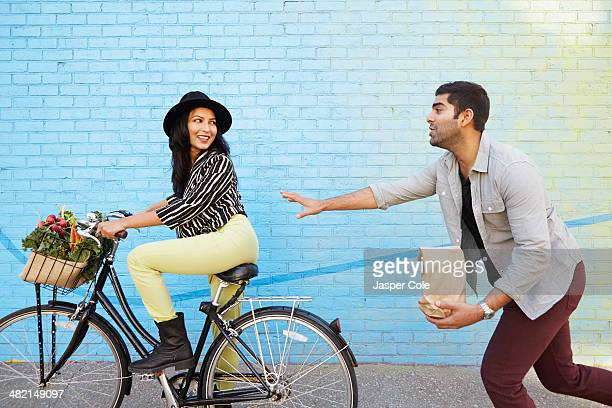 Indian man chasing girlfriend on bicycle