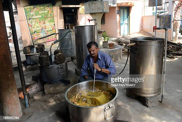 Indian man Chatursang Jadeja prepares a mixture of various herbs mixed with cow urine at a 'gaushala' cowpen run by the Shree Vardhman Jivdaya Kendra...