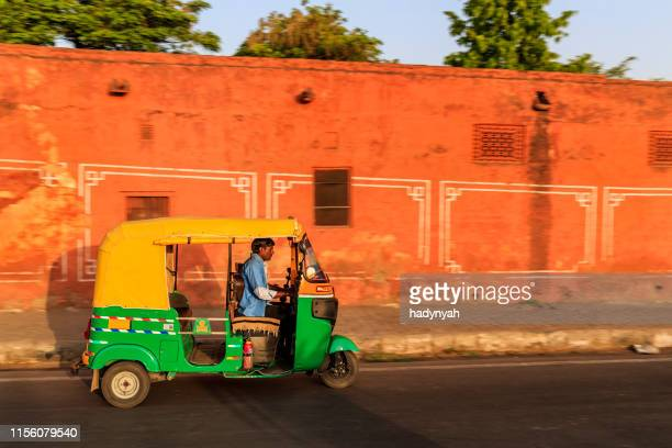 indian man drives auto rickshaw (tuk-tuk), india - auto rickshaw stock pictures, royalty-free photos & images