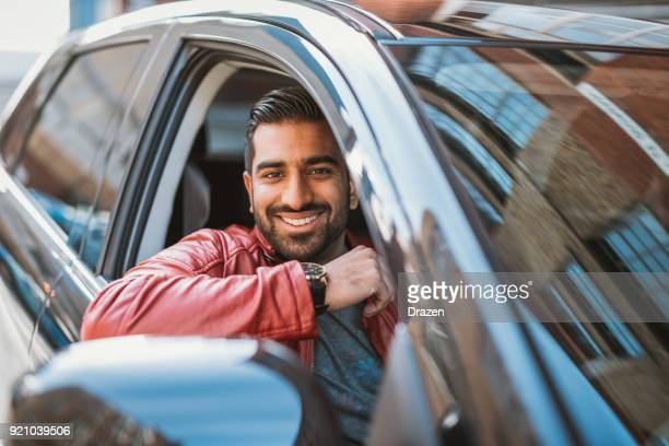 indian man driving luxury taxi - driver stock photos and pictures