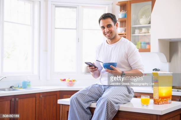 Indian man eating breakfast on kitchen counter