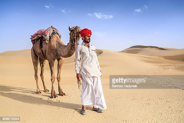 Indian man holding camel on sand dunes, Rajasthan, India