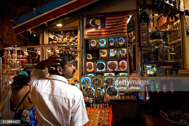 Indian man in front of a gift/souvenir shop inside the Batu Caves in Kuala Lumpur Malaysia The cave is one of the most popular Hindu shrines outside...