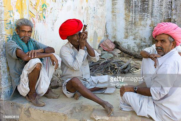 Indian man in traditional clothing smokes clay pipe while sitting with friends in Narlai village in Rajasthan Northern India