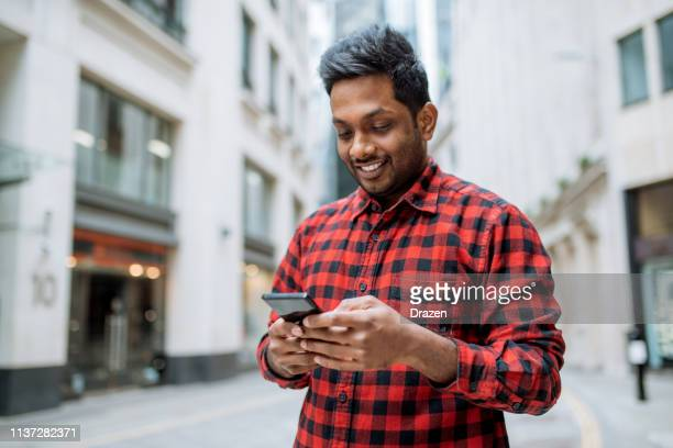 Indian man in UK using phone for online messaging