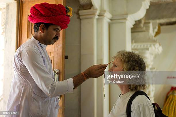 Indian man makes traditional bindi mark on tourist forehead in Hindu Temple in Narlai village in Rajasthan Northern India
