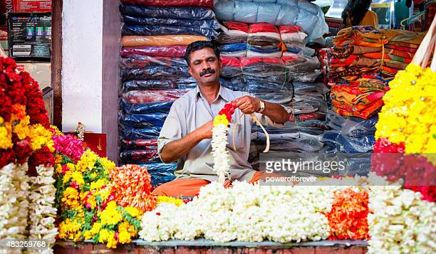 Indian man making flower necklaces at Market in Munnar, India.
