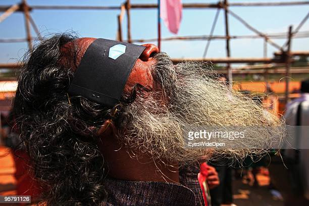 Indian man observes the rare Annular Solar Eclipse at the central stadium on January 15 2010 in Thiruvananthapuram Kerala South IndiaThis rare...