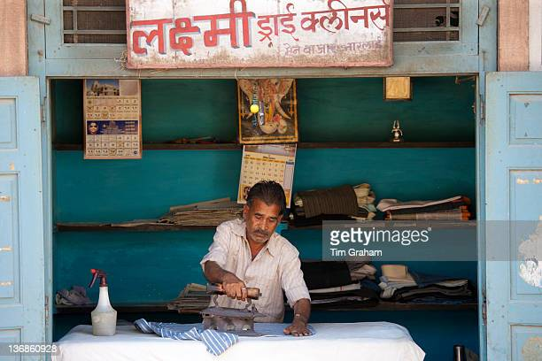 Indian man pressing clothes in his workroom in Narlai village in Rajasthan Northern India
