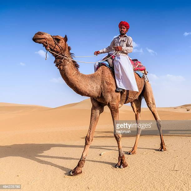 Indian man riding camel on sand dunes, Rajasthan, India