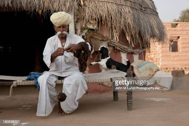 Indian man spins wool into yarn in his village in