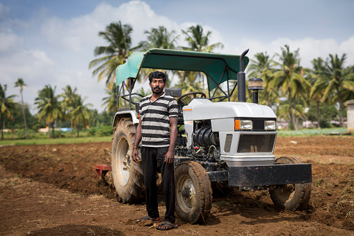 Indian man standing in farmland next to his tractor. - gettyimageskorea