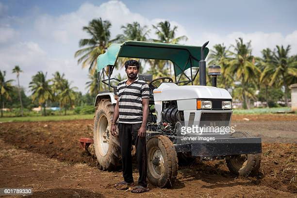 Indian man standing in farmland next to his tractor.