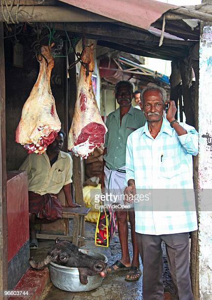 Indian man talking at the mobile phone at a butcher shop that offes meat and the head of a waterbuffalo in Kumily on January 02 2010 in Kumily near...