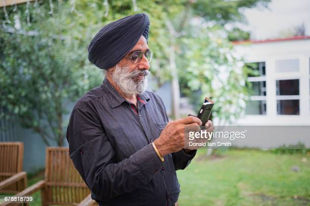 Indian man texting on cell phone