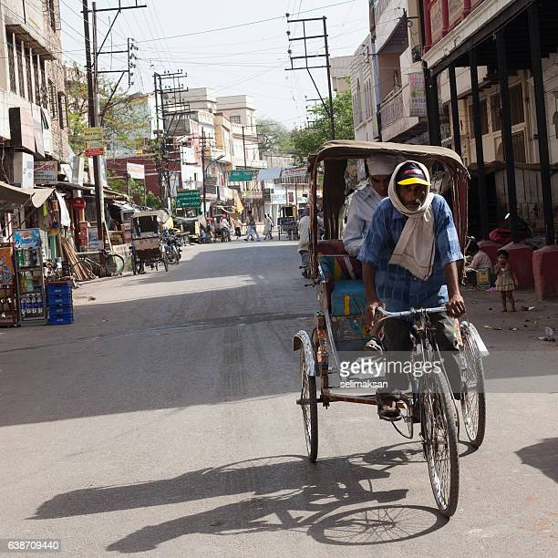 indian man transporting passengers with his cycle rickshaw - human powered vehicle stock photos and pictures