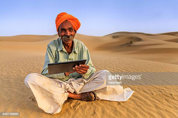 Indian man using a digital tablet, desert village, India
