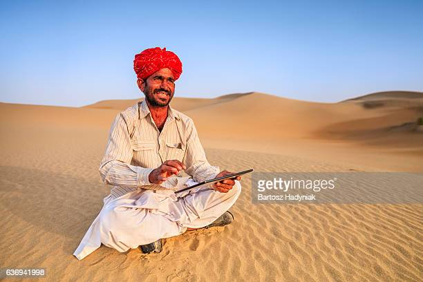 Indian man using a digital tablet, desert village, India