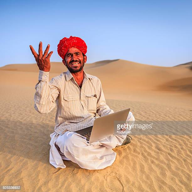 Indian man using a laptop, desert village, India