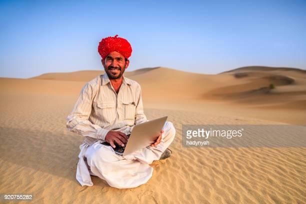 Indian man using a laptop, desert village, India