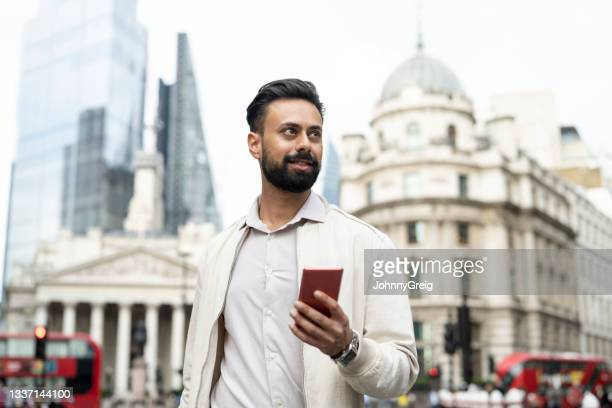 indian man walking through london's financial district - mid adult men stock pictures, royalty-free photos & images