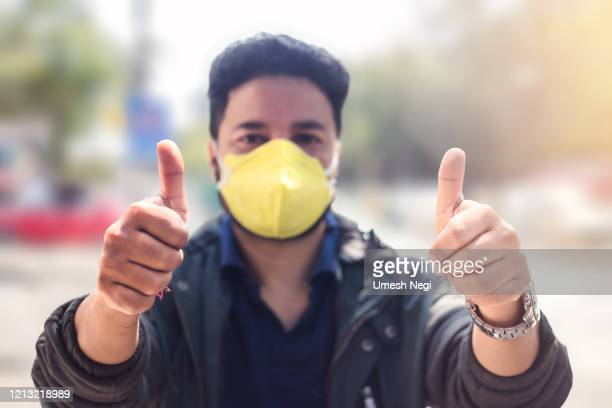 indian man wearing mask and showing thumbs up for protection against virus, dust, pollution and smog. - nose mask stock pictures, royalty-free photos & images