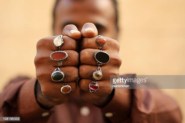 indian man wearing semi precious stone rings - human finger stock photos and pictures