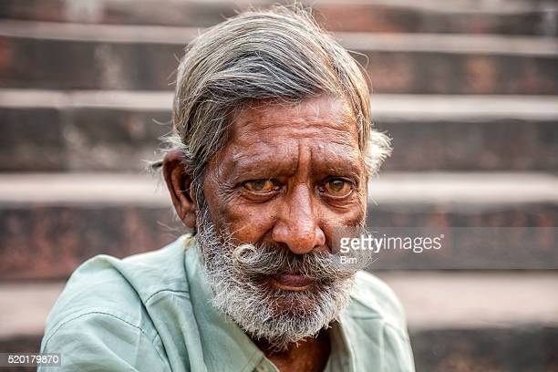 Indian man with moustache sitting on stairs, Delhi, India