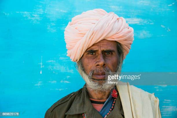 indian man with rose turban in front of blue house wall real people portrait india - jodhpur stock pictures, royalty-free photos & images