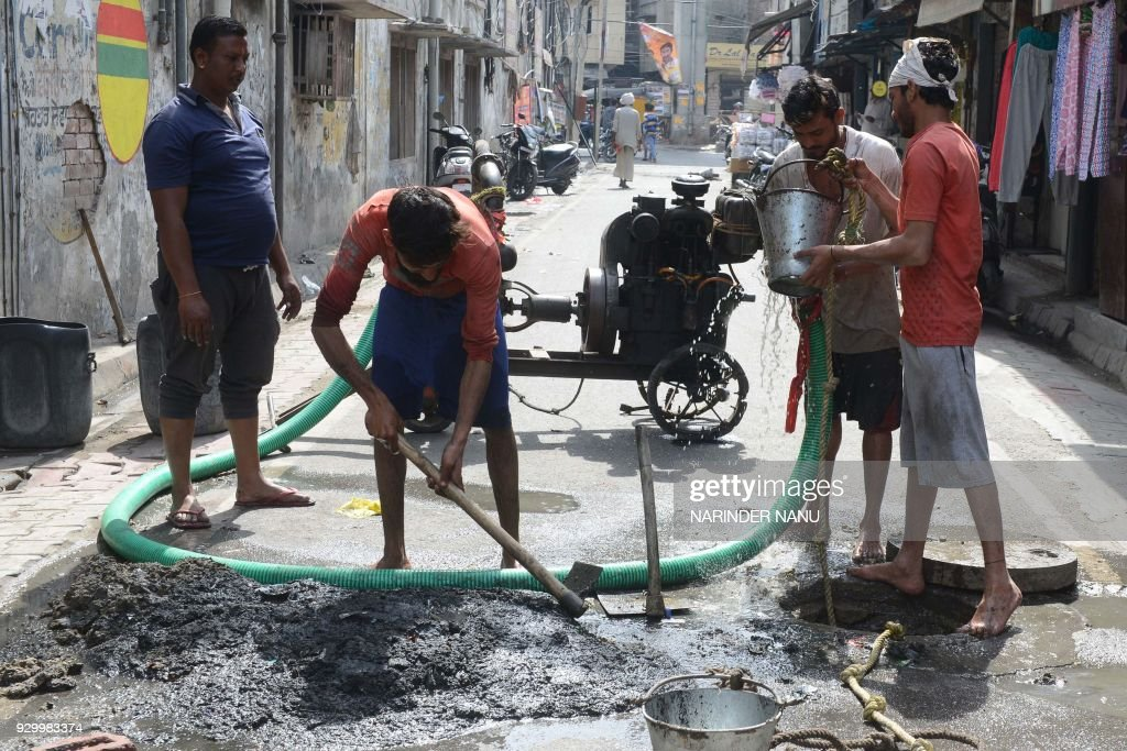 Indian manual labourers clean out sewage drains in Amritsar on March 10 2018 / AFP PHOTO / NARINDER NANU
