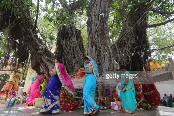 Indian married Hindu women tie a thread to a banyan tree on the occasion of 'Vat Savitri Amavasya Pooja' in Bhopal on May 15 2018 Vat Savitri Vrat is...