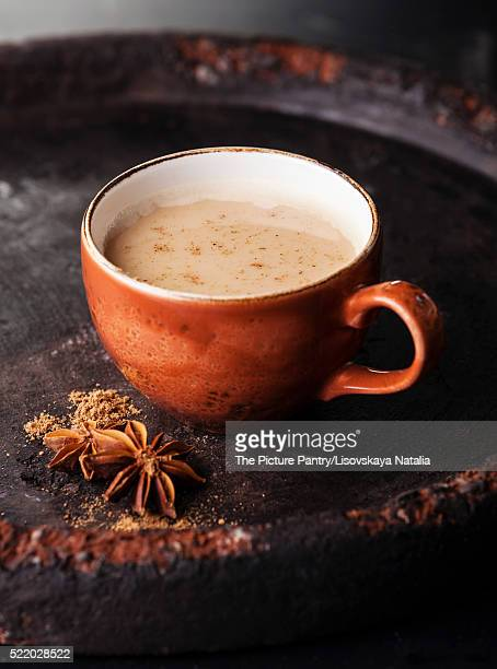 Indian masala tea with spices and milk on dark background