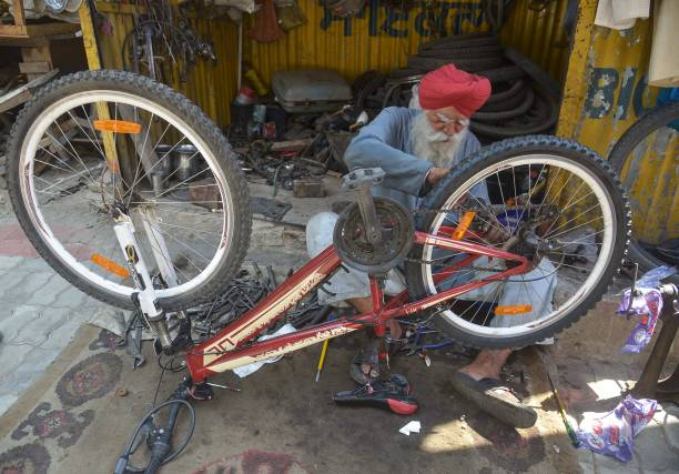 Indian mechanic Hardev Singh repairs a bicycle at his shop in Amritsar on May 30 2017 Singh said he earns around 300600 INR a day for his bicycle...