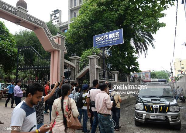 Indian media persons gather around police vehicle in front of Bishop's house to cover the Kerala state police investigation in relation to bishop...