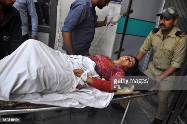 Indian medical and security officials use a trolley as they transfer injured villager Zatoon Bi into The Government Medical College Hospital in Jammu...
