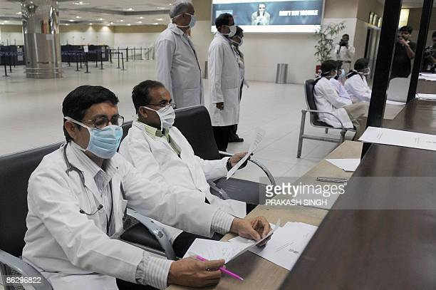 Indian medical officers wait at a counter to screen arriving air travellers for swine flu symtoms as precautionary measures at the Indira gandhi...