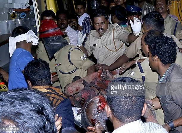 TOPSHOT Indian medical officials and bystanders carry an injured man into an ambulance enroute to a hospital after an explosion and fire at The...