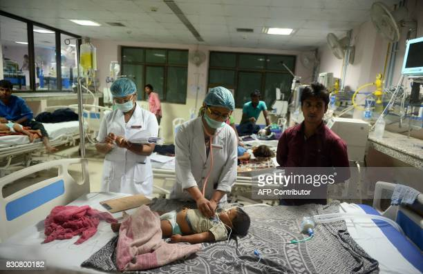 TOPSHOT Indian medical staff attend to a child admitted in the Encephalitis ward at The Baba Raghav Das Hospital in Gorakhpur in the northern Indian...