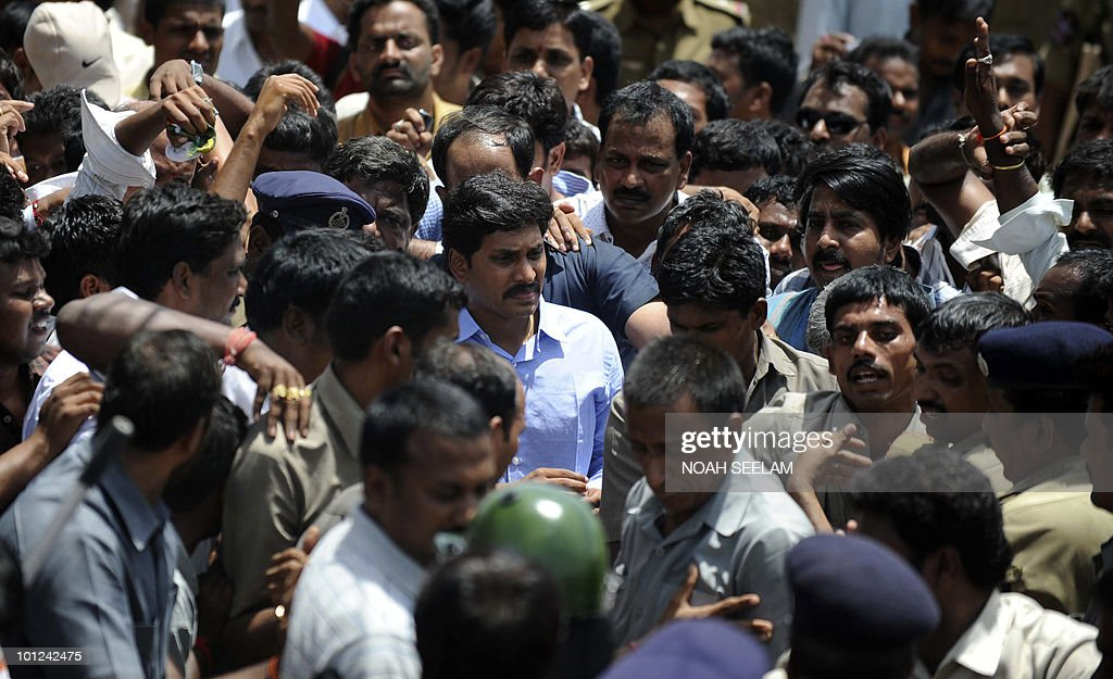 Indian Member of Parliament (MP) Y. S. Jaganmohan Reddy (C-blue shirt) walks after disembarking from a train carriage at Wangapalli Railway Station in Nalgonda District, some 80kms north of Hyderabad on May 28, 2010, following his arrest by police authorities. Reddy, the son of the late Chief Minister of Andhra Pradesh Y. S. Rajasekhara Reddy has planned a �Odarpu Yatra' (consoling tour) to comfort over 70 families whose members allegedly died either due to heartbreak or committed suicide following the death of his father in September 2009. AFP PHOTO/Noah SEELAM