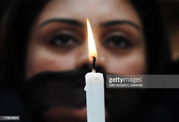 Indian members of a social organisation Our City Our Right holds a candle during a silent protest following the recent gang rape and murder of a...