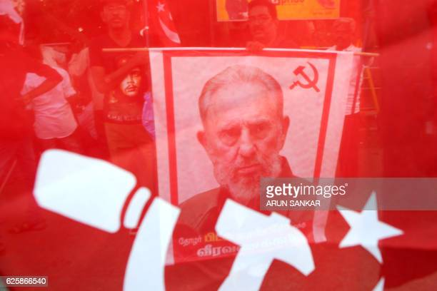 Indian members of Communist Party of India carry placards bearing the image of former Cuban president Fidel Castro during a remembrance rally in...