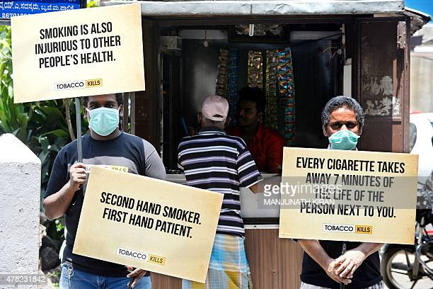 Indian members of staff from a cancer hospital hold placards in front of a roadside tobacco stall during an antismoking campaign event in Bangalore...