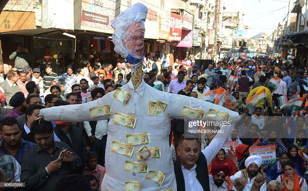 Indian members of the Congress party pose for media holding an effigy of Indian Prime Minister Narendra Modi during a protest in Amritsar on November.
