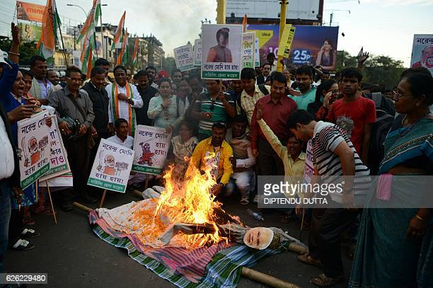 Indian members of the Congress Party shout slogans and burn an effigy of Prime Minister Narendra Modi during a protest against demonetisation in...