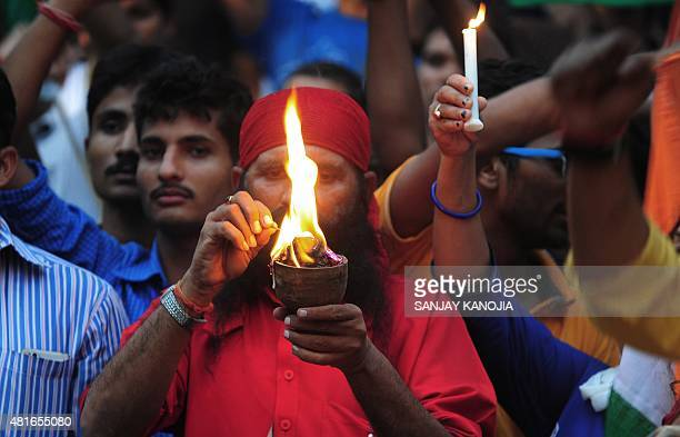 Indian members of the Jai Hind Foundation hold candles during an event to mark the 109th birth anniversary of Indian freedom fighter Chandra Shekhar...