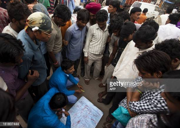 Indian members of the NGO Child Survival India draw a female body to help Indian truck drivers understand sex and the human body during an HIV...