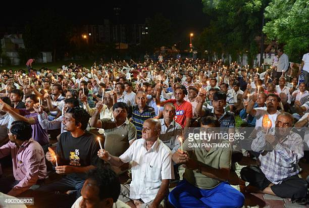 Indian members of the Patel Patidar community participate in a candlelight vigil in Ahmedabad on September 26 2015 in memory of eight members of the...