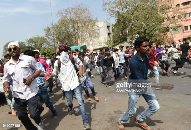 Indian members of the Scheduled Castes run amid clashes with security personnel during a protest against a Supreme Court order that allegedly diluted...