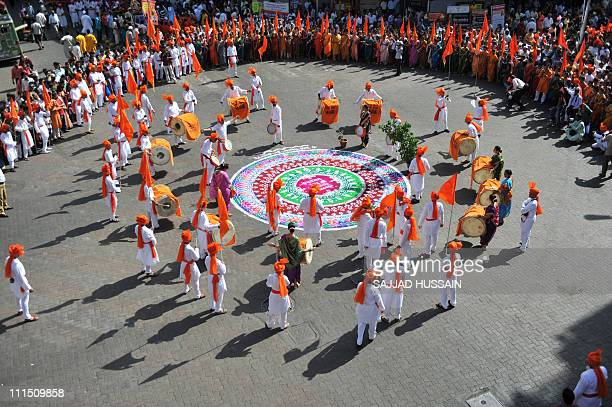 Indian men and women dressed in traditional attire walk around the main procession area to celebrate 'Gudi Padwa' or the Maharashtrian new year in...
