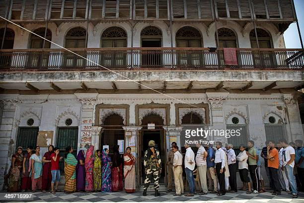 Indian men and women lineup on separate sides to vote at a polling station on May 12 2014 in Varanasi India Indians voted in the ninth and final...